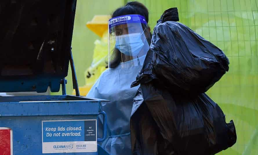 A worker removes medical waste from the Arcare Maidstone aged care facility in Melbourne on Monday.