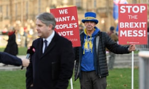 Anti-Brexit protester Steve Bray holds two of his placards as Conservative MP Philip Davies conducts a TV interview on College Green, outside the Houses of Parliament.