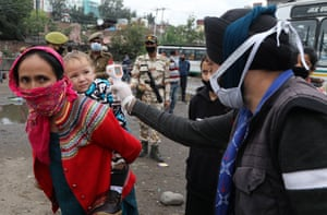 The temperature of stranded passengers is checked at the general bus stand during lockdown in Jammu