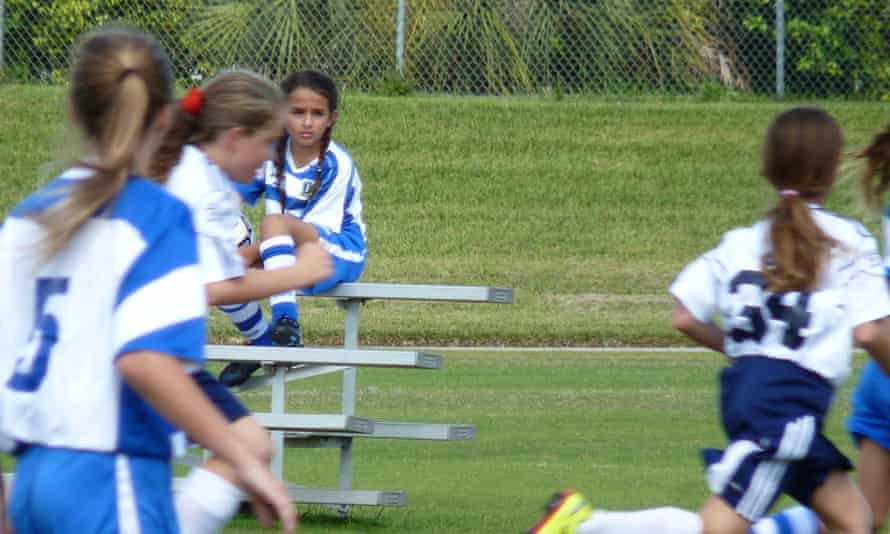 jazz jennings sits on the bench in soccer uniform