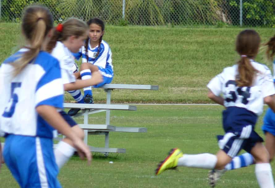 Jazz Jennings sitting on a bench while kids play soccer