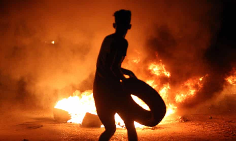 A demonstrator burns tyres during protests last month in the southern Iraqi city of Basra.