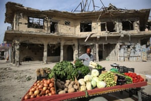 An Iraqi man sells vegetables in front of a ruined building in the old city of Mosul