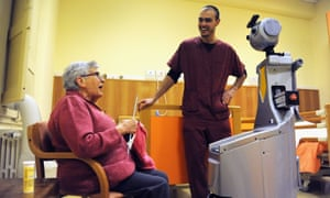 A resident of the San Lorenzo nursing home with Robot-Era and her physical therapist