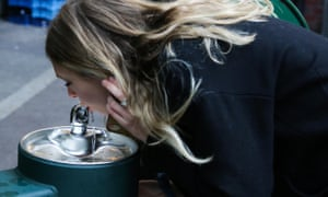 Woman uses a water fountain in Borough Market, London.