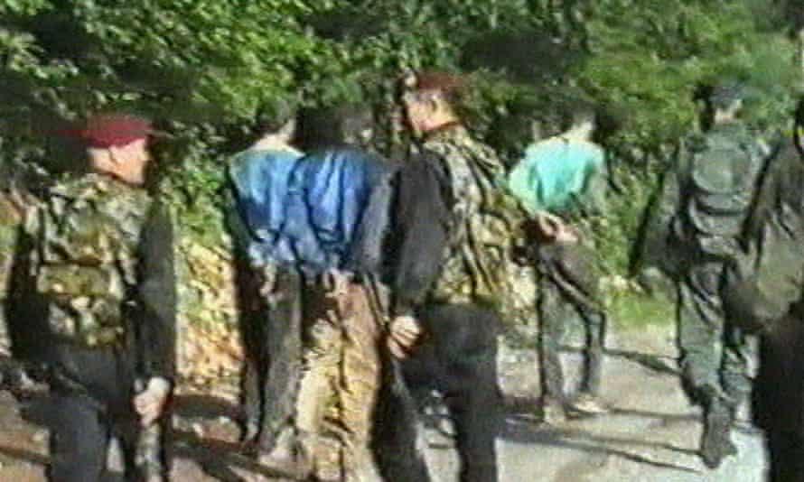 Serbian paramiltaries lead away Bosnian Muslim civilian prisoners who had been taken from Srebrenica.