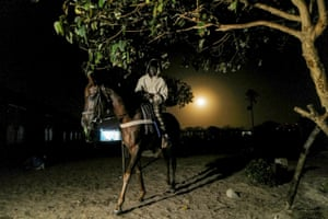 A stable boy rides a horse into the night