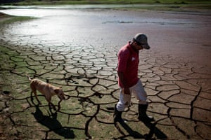 A resident walks his dog across the dry bottom of the Paraibuna dam, part of São Paulo's Cantareira water system.