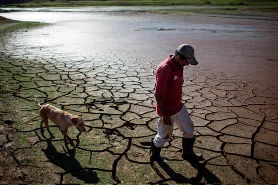 A resident walks his dog across the dry bottom of the Paraibuna dam, part of São Paulo's Cantareira water system.
