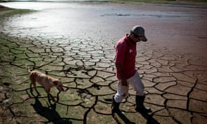 A resident walks with a dog across the drying bottom of the Paraibuna dam, Brazil.