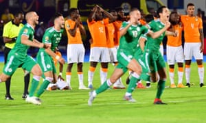 Ivory Coast players react in the background after Algeria condemned them to elimination in a quarter-final penalty shootout.