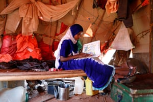 Zeinab, 14, reads an English book as she sits inside her shelter