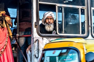 Man in turban looking from bus window with rickshaw in foreground.  Photographer: George Turnbull: While in Dholpur in Rajasthan, India, I got up early to scour the streets for photo opportunities and managed to get this shot of an early-morning commuter at the local bus station. Worth getting up early for, I think.