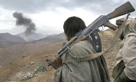 An Afghan mujahideen fighter watches as US warplanes bomb positions held by al-Qaida in the Tora Bora mountains in 2001.