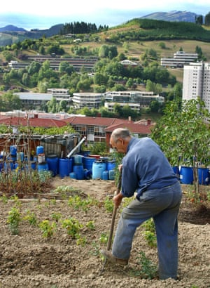 A man works on his land in the mountains overlooking the Mondragon Cooperative.