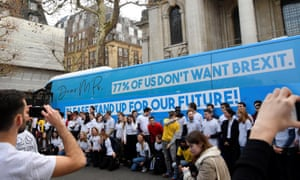 Campaigners gather beside a bus covered in a slogan promoting the pressure group Our Future, Our Choice (OFOC) near the Houses of Parliament in London.