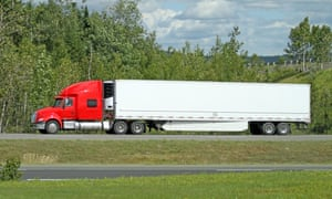 Semi Truck Transporting Freight On An Interstate Highway, Side ViewSide view of a semi tractor trailer truck hauling a load of freight on an interstate highway.