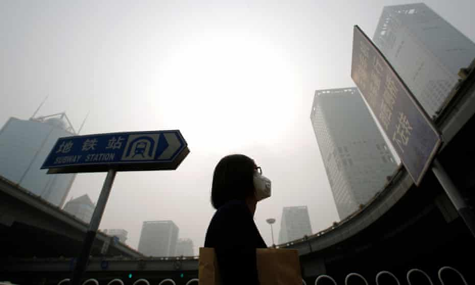 A woman wearing a mask walks in heavy smog in Beijing. Every year about one in 10 babies are born prematurely, according to the WHO.