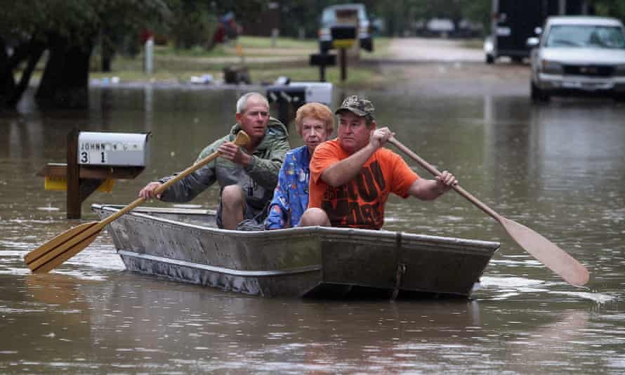 Two sons evacuate their mother from her flooded home near Downsville, Texas.