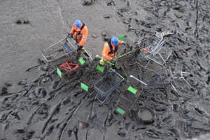 Workers collect supermarket trollies from the Thames in Gravesend, England