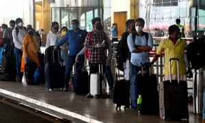 Passengers queue to enter Mumbai airport, as domestic air travel was lifted after two months on the ground due to the coronavirus pandemic.