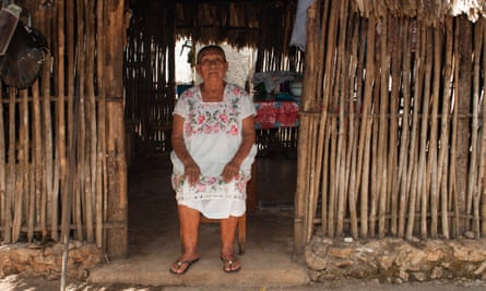 Luis Góngora's mother, Estela, sits at the entrance to the traditional Mayan house where her son and his wife lived when they were first married.