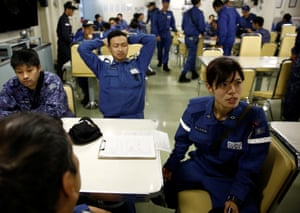 Ayako Yoneda, right, a 29-year-old firefighter and engineer on the Kaga, sits with the crew