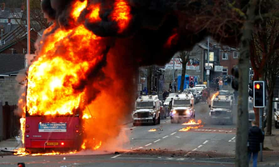 Police vehicles are seen behind a hijacked bus burns on the Shankill Road as protests continue in Belfast.