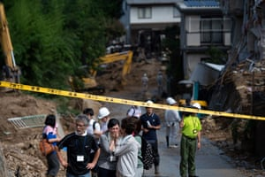 People look out at a damaged street in Kumano