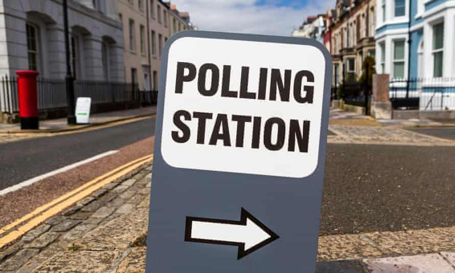 Polling Station sign with right pointing arrow on a typical British street.