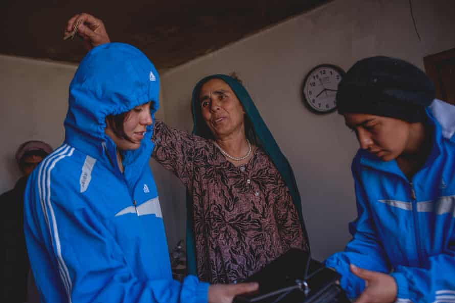 Nazira and Nazima's mother blesses them by waving money above their heads for good luck before they head out to compete in the Afghan Mountain Challenge.