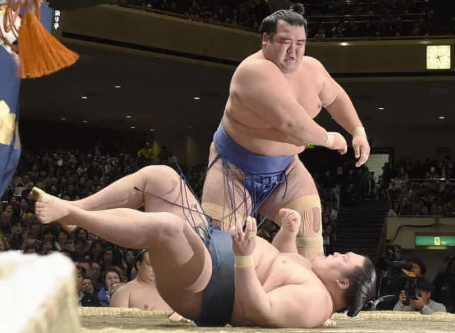 Kotoshogiku throws Goeido down in the ring to win the championship