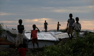 Internally displaced people (IDPs) stand on roofs in a camp run by the UN mission in South Sudan near the town of Malakal
