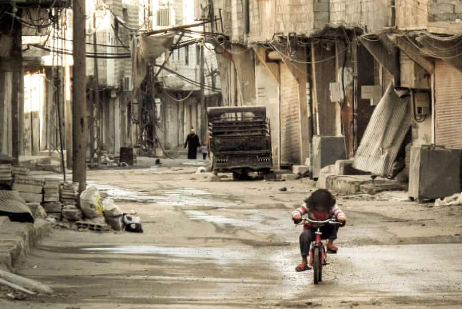 A Syrian girl rides her bicycle in an almost deserted street in Damascus in 2013