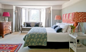 Bedroom with a white and grey paint job and artwork and lampshades in orange and pink, at the Fritton Arms, Norfolk.