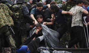 Migrants fall during clashes with police near Gevgelija, Macedonia, on Saturday.
