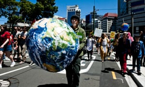 A man holding a large blow up globe participates in the march on New Zealand parliament in Wellington on Saturday to call for more action on climate change.