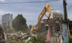 An excavator works to demolish a house in the Vila Autodromo slum in Rio de Janeiro.