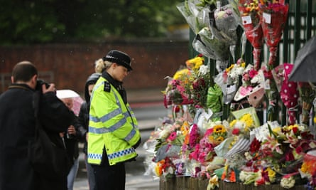 A police officer stops to look at flowers laid close to the scene in Woolwich where Fusilier Lee Rigby was killed in May 2013.