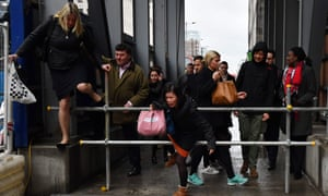Commuters take a shortcut through a construction site during the 24-hour tube strike.