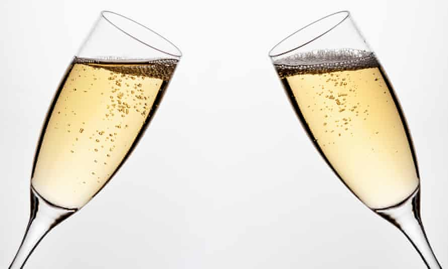 Two full champagne flutes angled for a toast