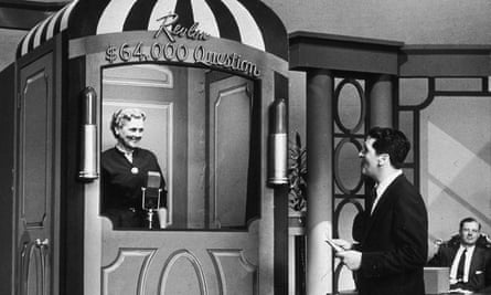 Host Hal March quizzes a contestant on The $64,000 Question in 1955.