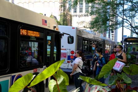 Commuters wearing protective masks board a bus on Michigan Avenue in Chicago, Illinois.