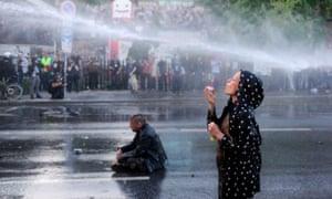 A protester blows bubbles