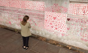 A woman pauses to look at the hearts and personal tributes to some of those lost to Covid-19 in London.