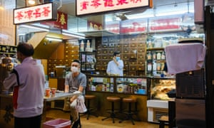 Workers at the a taditional Chinese medicine shop wear face masks as a precaution against the spread of coronavirus.