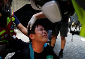 A protester has his eyes cleaned after teargas was fired