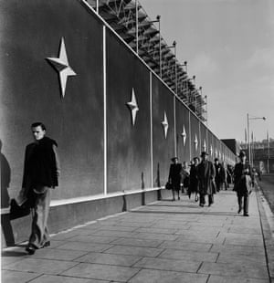 Commuters walk past another screen outside the site, featuring a version of the Festival Star - the emblem of the Festival of Britain - designed by Abram Games.(GNM Archive ref: JHB/1/3/43 box 3)