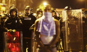 A man stands in front of police officers as curfew approaches