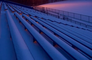 Snow blankets the Roxborough High School football field bleachers before dawn in Philadelphia, Pennsylvania